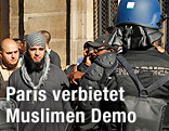 Polizisten versperren einem Demonstranten in Paris den Weg